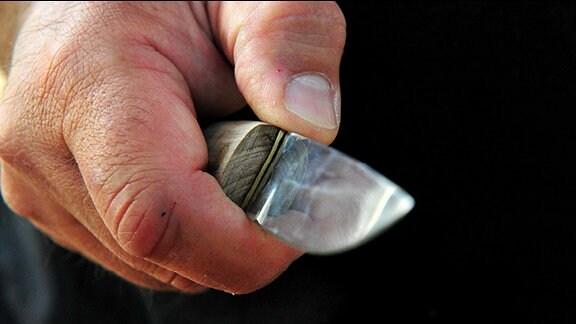 Eine Hand hält ein Messer.