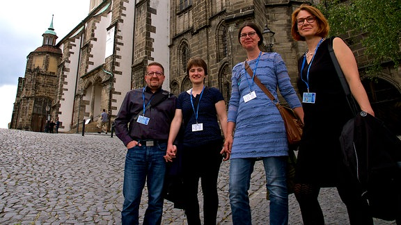 vier Menschen stehen vor einer Kirche
