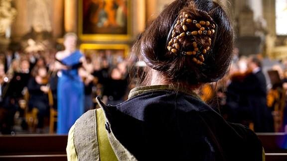 Frau sitzt in einer Kirche und hört einem Konzert zu