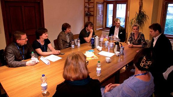 eine Gruppe Menschen sitzt an einem Tisch in einem Raum