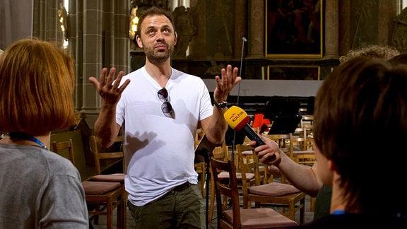 ein Mann steht in einer Kirche und spricht in ein Mikrofron