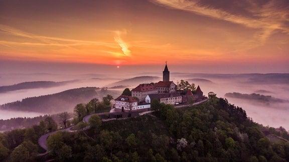 Der Sonnenuntergang färbt den Himmel über der Leuchtenburg in bunte Farben