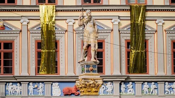 An der Fassade des Kunsthaus Erfurt hängt goldene Folie. Im Vordergrund steht die Statue Der Römer.