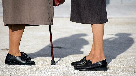 Schuhe und Mantel von zwei älteren Frauen.