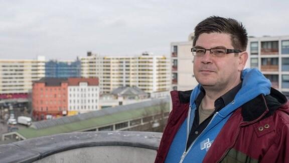 Sozialwissenschaftler Andrej Holm trägt eine Sportjacke. Hinter ihm sind Häuserschluchten zu sehen.