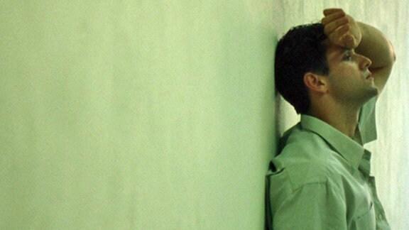 Junger Mann an eine Wand gelehnt und sich die Hand an die Stirn haltend.