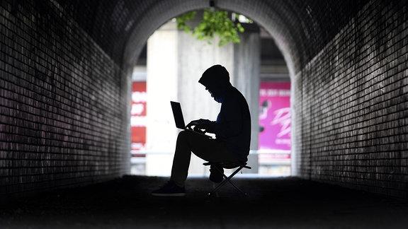 Symbolbild Computerhacker - Ein verhüllter Hacker sitzt in einem dunklen Tunnel.