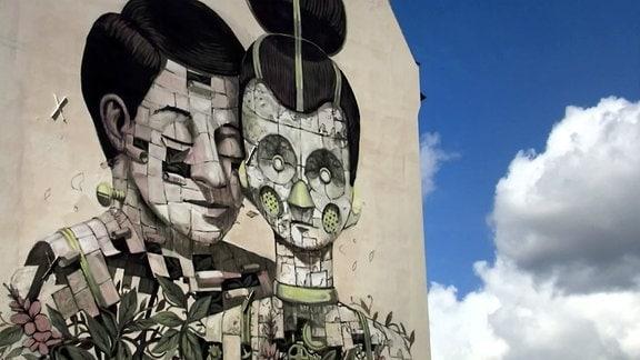 Kunst an der Hauswand - Ein Mann schmiegt sich an eine Roboterfrau.
