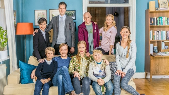Eine Gruppe bestehend aus neun Personen posiert als Familie auf einem Sofa.