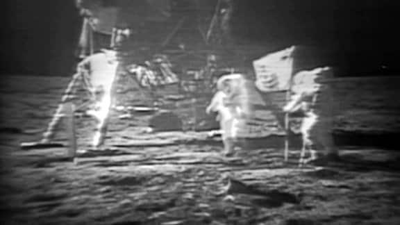 Astronauten stellen eine Flagge auf dem Mond auf.
