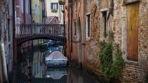 Ein kleiner Kanal und eine Brücke in der Lagunenstadt Venedig in Italien.