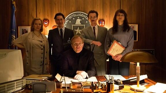 Menschen posieren hinter einem Schreibtisch