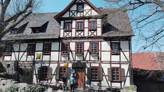 """Die Gaststätte """"Klausenhof"""" in Bornhagen. Ein weiß braunes Fachwerkhaus mit schwarzem Dach."""