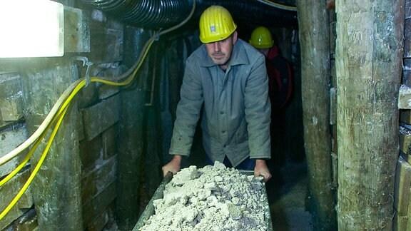 Bergleute schieben Loren durch die Stollen der Kaolingrube Seilitz.