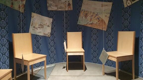Detail zur Ausstellung: Stühle in einem blauen Raum.