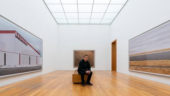 Der Fotograf Andreas Gursky sitzt vor seinen Werken l-r Bauhaus 2020, Ohne Titel III 1996 und Rhein III 2018 im Museum der bildenden Künste MdbK in Leipzig.