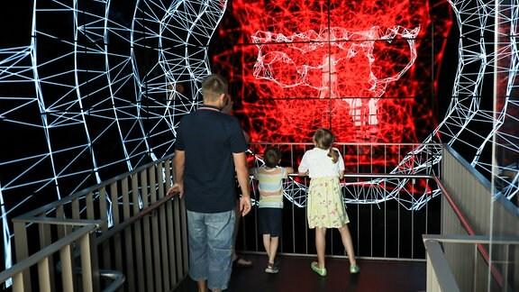 Ein Mann und zwei Kinder stehen vor einer Projektion.