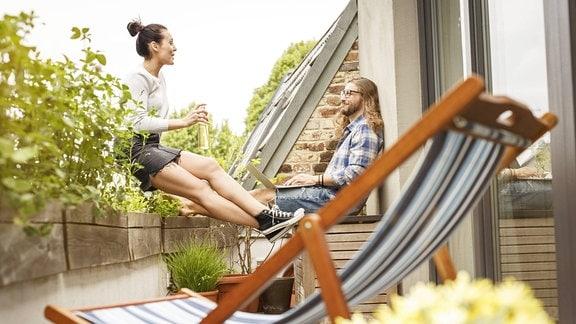 Zwei junge Leute auf einem Balkon