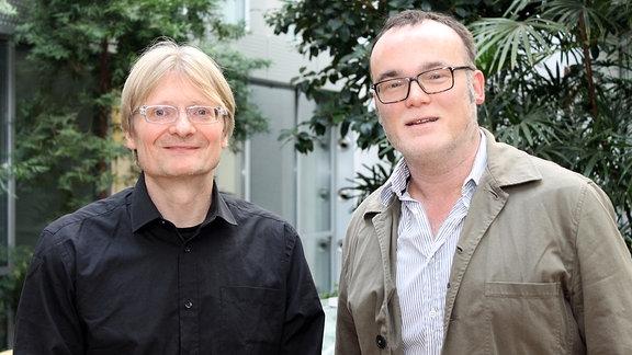Zwei Männer stehen nebeneinander und lächeln