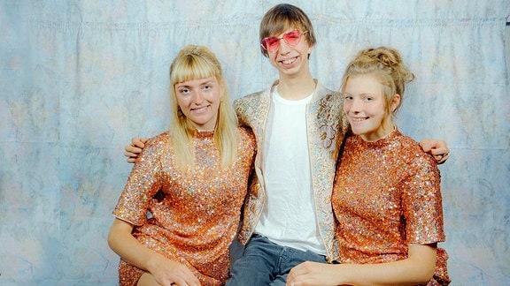 Ein junger Mann zwischen zwei jungen Frauen