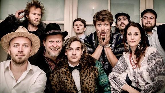 Die neun Mitglieder der Band Batiar Band stehen zusammengerückt vor einer Fensterfront