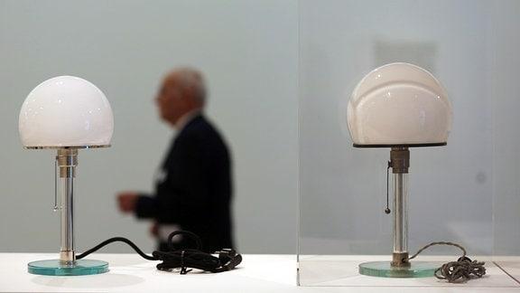 Ein Mann geht am 31.03.2016 in Bonn (Nordrhein-Westfalen) an dem Original der Tischlampe von Wilhelm Wagenfeld (r) und einem Nachbau (l) vorbei.