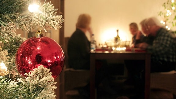 Familie sitzt an Heiligabend gemeinsam am Tisch