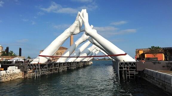 Riesige hand-Skulpturen schlagen eine Brücke über einen Kanal