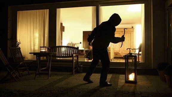 Symbolbild Einbruch, Einbrecher will in ein Haus eindringen, schleicht sich auf der Terrasse an.