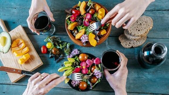 verschiedene Salate und Weingläser auf einem Tisch