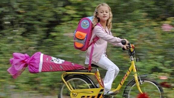 Ein kleines Mädchen mit Schultüte auf dem Fahrrad