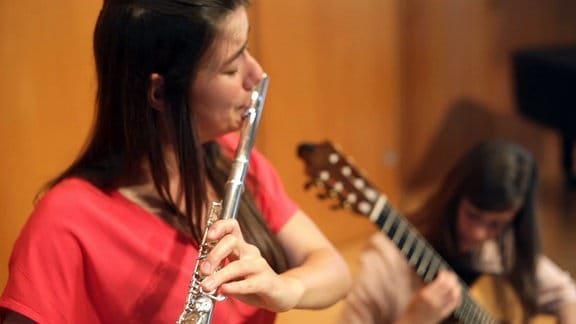 Zwei junge Frauen; eine spielt Querflöte, die andere Gitarre