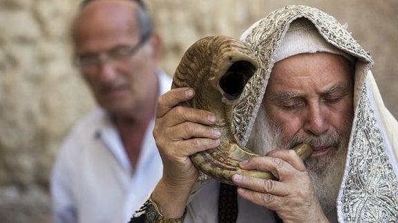 Ein orthodoxer jude bläst an der Klagemauer in Jerusalem, Israel, ein Schofar, das Horn eines Widders.