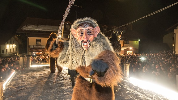 Mit kunstvoll handgeschnitzten Masken und wilden Pelzgewändern verkleidete Menschen