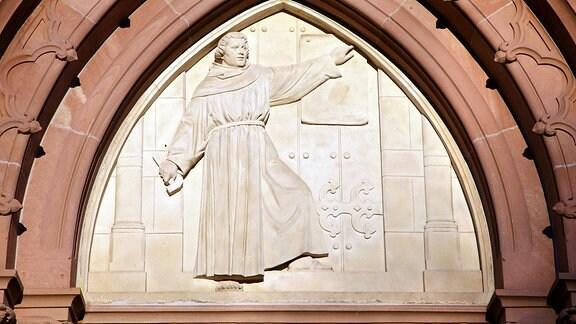 Der Spitzbogen am Westportal der evangelische Lutherkirche in Rudolstadt in Thueringen zeigt auf einem Flachrelief Luther beim Thesenanschlag