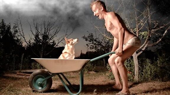 Ein halbnackter Mann mit einer Schubkarre, in der ein Hund sitzt