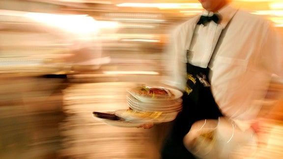 Ein Kellner mit benutzten Tellern