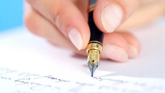 eine Hand mit Federhalter beim Schreiben auf ein Blatt Papier