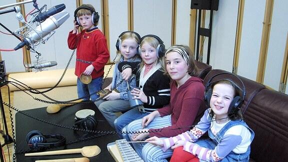 Kinder mit Kopfhörern in einem Studio