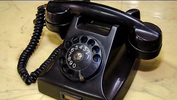Ein altes schwarzes Telefon mit Wahlscheibe.