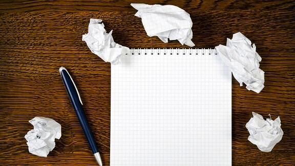 Ein Notizblock mit Kugelschreiber auf einem Holzschreibtisch