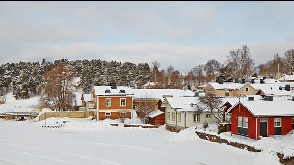 Zugeschneite Holzhäuser an einem Fluss in Porvoo Stadt (Finnland).