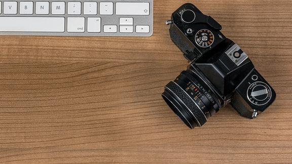 Neben einer neueren Tastatur liegt eine ältere Kamera.