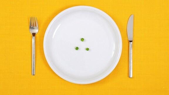 Auf einer gelben Tischdecke steht ein Gedeck mit 3 Erbsen.