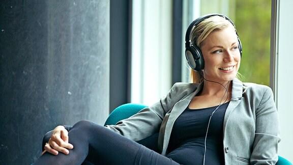 Eine junge Frau mit Kopfhörern sitzt in einem Sessel