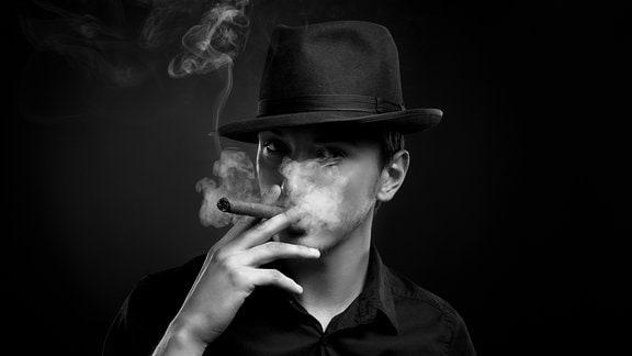 ein Mann mit Hut raucht Zigarre