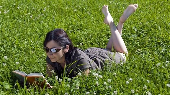 Junge Frau mit Sonnenbrille liegt auf einer Wiese und liest ein Buch.