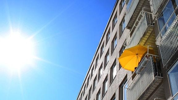 Sonnenschein und ein Wohnhaus mit Balkonen.