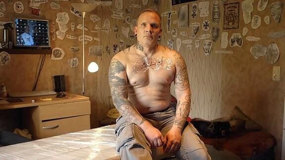 Ein tätowierter Mann sitzt auf einer Liege
