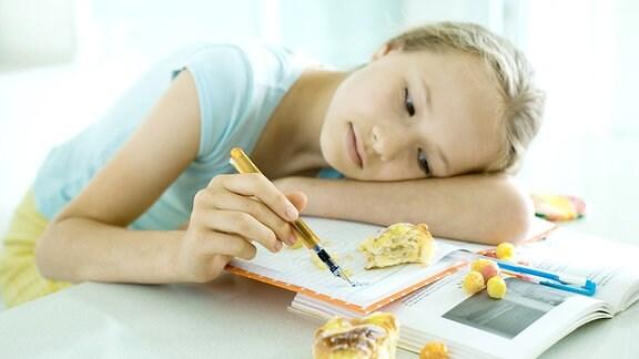 Ein Mädchen liegt mit dem Kopf auf Schulbüchern und kritzelt in einem Heft